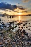 日落多岩石的海滩 免版税库存照片