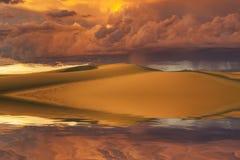 日落天空和沙丘的反射在水中 库存图片