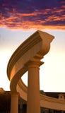 日落天空的背景的古色古香的柱廊 免版税图库摄影