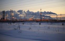 日落天空背景的精炼厂 冷淡的多雪的冬天晚上 免版税图库摄影