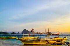 日落天空闪烁海峭壁的美妙的看法在天际和小船的在一个沙滩旁边停泊了 免版税库存照片