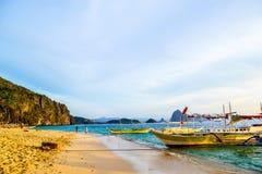 日落天空闪烁海峭壁的美妙的看法在天际和小船的在一个沙滩旁边停泊了 图库摄影
