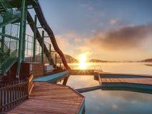 日落岸和雪橇在湖滑, 与滑轨道的高梯子塔 免版税库存照片