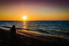 日落岸的度假者 库存照片