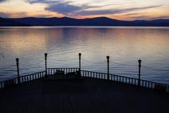 日落或日出在一个码头在山湖 免版税图库摄影