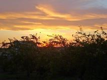 日落或日落—太阳的上部边缘的失踪的片刻在天际下的 库存照片