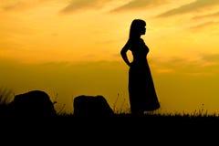 日落摇滚的剪影的女孩 免版税图库摄影