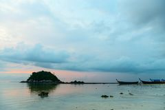 日落时间的风平浪静与海岛和小船 免版税库存图片