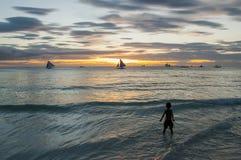 日落海岸的男孩 免版税库存照片