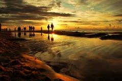 日落海滩和走的人民 免版税库存照片