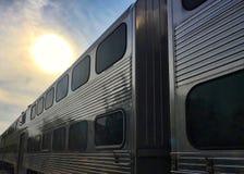 日落消失入它的天空和市郊火车在滴下乘客以后 库存照片