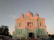 日落温和的玫瑰色光在三位一体大教堂的Diveyevo和蓝天的 免版税库存照片