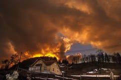 日落灼烧的天空的背景的一个小屋 库存照片