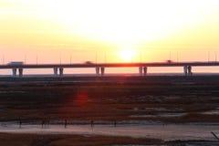 日落焕发,世界的最长的桥梁有车在交通 免版税库存图片