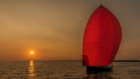 日落照亮的红色大三角帆 图库摄影