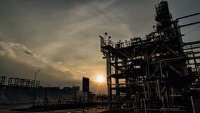 日落由后照的石油工业结构 免版税库存图片