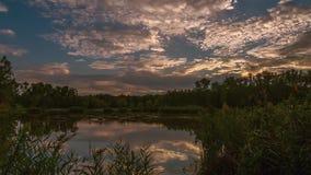 日落的一个迷人的湖在移动天空的云彩下 定期流逝,录影 股票录像