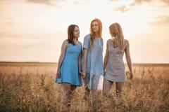 日落的三个女孩 库存图片
