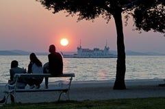 日落的人们在海上的天际 免版税库存图片