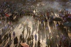 日落的人们在著名Djma El fnaa在马拉喀什摆正 免版税库存图片