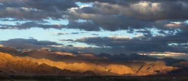 日落的全景在山谷的:微明,一部分的山脉绘了太阳以黄色,巨大的光芒 库存照片