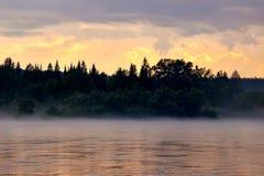 日落的全景在河下雾的夜晚 免版税库存照片