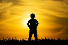 日落的剪影男孩 免版税库存图片
