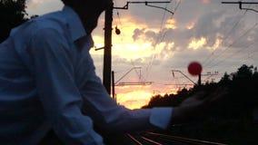 - 日落的变戏法者在一条腿平衡在铁路附近并且做危险把戏 股票录像