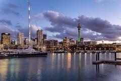 日落的奥克兰港口与美丽的游艇和城市地平线 免版税图库摄影