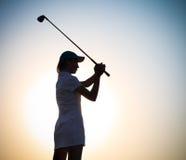 日落的女性高尔夫球运动员 库存照片