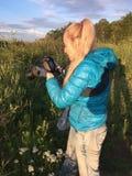日落的妇女拍摄在森林的边缘的一棵草 免版税库存图片