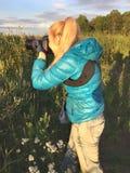 日落的妇女拍摄在森林的边缘的一棵草 库存图片