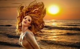 日落的妇女海上 免版税库存图片