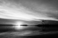 日落的射击在一个湖的,当下来的太阳后边和海岛 免版税库存照片