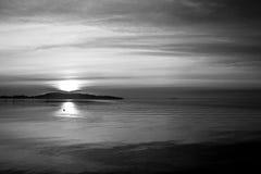 日落的射击在一个湖的,当云彩和许多对角线创造的太阳下来后边和海岛和 图库摄影