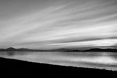 日落的射击在一个湖的,当云彩和许多对角线创造的太阳下来后边和海岛和 免版税图库摄影