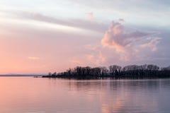 日落的射击在一个湖的,有美好的温暖的颜色的和云彩和树反射在水 免版税图库摄影