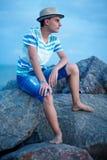 日落的少年在海边附近 库存照片