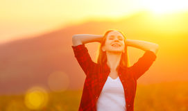 日落的愉快的妇女在自然iwith开放手上 免版税库存照片