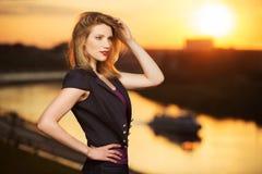 日落的愉快的年轻时尚妇女 免版税图库摄影
