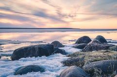 日落的抽象图象在湖的有熔化的冰的在早期的春天 金黄小时颜色、草和石头 图库摄影