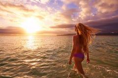 日落的无忧无虑的妇女在海滩 假期生命力hea 免版税库存图片