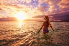 日落的无忧无虑的妇女在海滩 假期生命力hea 免版税图库摄影