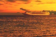 日落的海与在水和剧烈的云彩,在天际的一个大巡航划线员的轻的波纹 库存图片