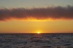日落的海洋与上面小条云彩 库存图片