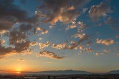日落的照片和云彩以及小镇的基础设施 免版税库存图片