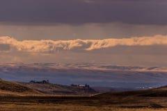 日落的爱达荷大农场在小雪以后在蓝天和残破的云彩下 库存照片