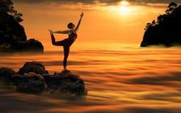 日落的瑜伽妇女 免版税库存图片