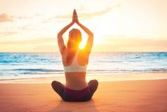 日落的瑜伽妇女 库存照片