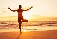 日落的瑜伽妇女 免版税库存照片